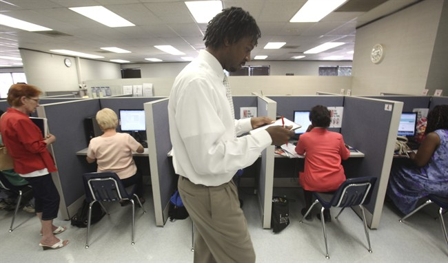 Texas Workforce Commission supervisor David Serrell manages job seekers time on computers at the Workforce Solutions of Greater Dallas job resource center in Richardson, Texas Tuesday, July 5, 2011. The number of people applying for unemployment benefits fell last week to the lowest level in seven weeks, although applications remain elevated. (AP Photo/LM Otero).