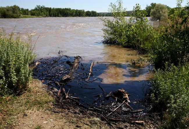 Oil swirls in a flooded gravel pit in Lockwood, Mont. after a pipeline break early Saturday, July 2, 2011.