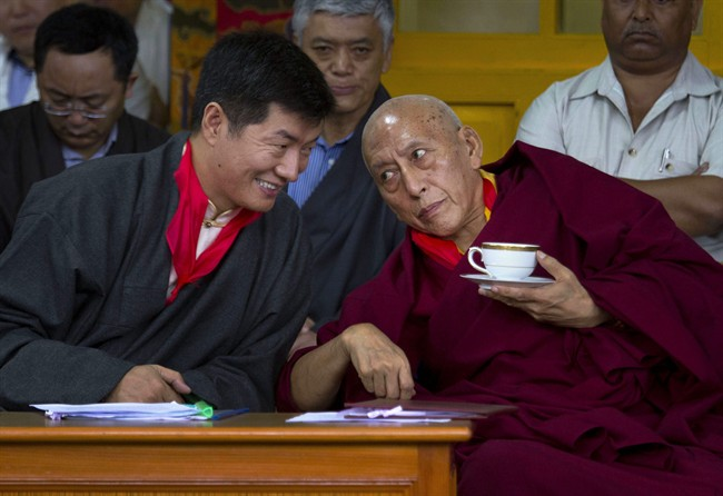Lobsang Sangay, left, the new prime minister of Tibet's government in exile, speaks with outgoing Prime Minister Samdhong Rinpoche during his swearing-in ceremony at the Tsuglakhang Temple in Dharmsala, India, Monday, Aug. 8, 2011. (AP Photo/Ashwini Bhatia).