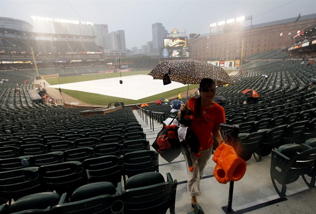 Ashley Lentz, of New Oxford, Pa., leaves her seat to find shelter during a rain delay before a scheduled baseball game between the Toronto Blue Jays and the Baltimore Orioles in Baltimore, Saturday, Aug. 6, 2011. (AP Photo/Patrick Semansky).