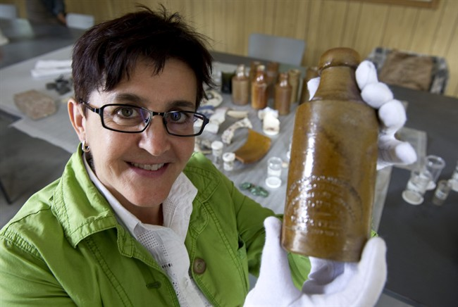 Louise Pothier, director of exhibitions at Montreal's Pointe-a-Calliere archeological and history museum, holds up a beer bottle found in the remains of what was supposed to have been the first permanent parliament of what was then the United Province of Canada, Monday, August 22, 2011 in Montreal. THE CANADIAN PRESS/Paul Chiasson.
