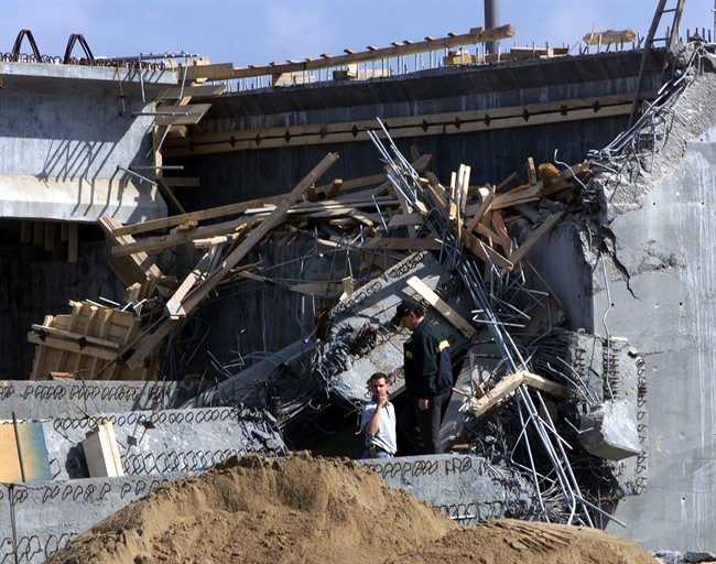 Investigators search through the rubble of a collapsed overpass in Laval, Que. in this June 19, 2000 photo. Two years of corruption scandals in Quebec have reached boiling point with the leak of a new study that reportedly describes an elaborate system of construction scams.The study from a newly created anti-corruption unit reportedly links the Mafia and criminal biker gangs to the construction industry, and the industry to political parties. THE CANADIAN PRESS/Ryan Remiorz.
