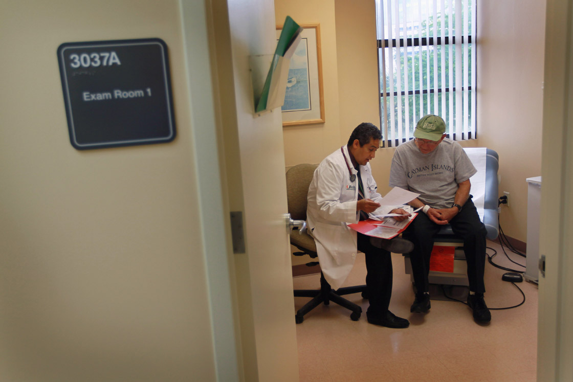 Dr. Olveen Carrasquillo (L), Chief of General Internal Medicine University of Miami, sits with Juan Gonzalez as he conducts a checkup on him.