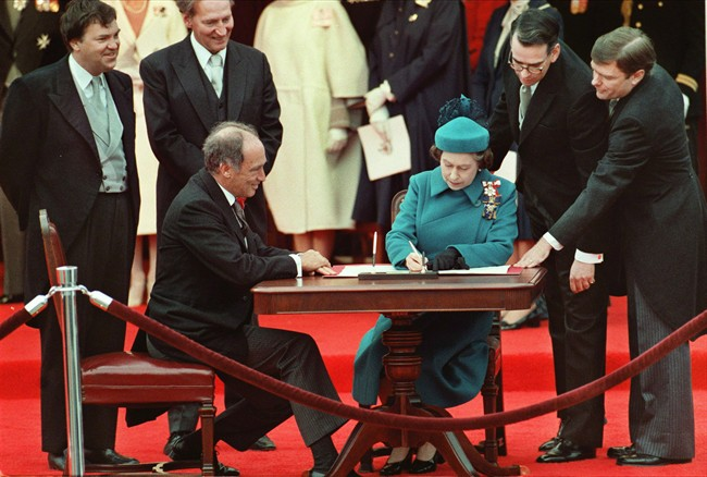 Queen Elizabeth II signs Canada's constitutional proclamation in Ottawa on April 17, 1982 as Prime Minister Pierre Trudeau looks on.