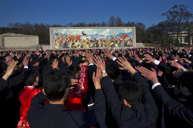 North Koreans dance together beneath a mosaic painting of the late leader Kim Il Sung during a mass folk dancing gathering in Pyongyang Thursday, April 11, 2013, to mark the anniversary of the first of many titles of power given to leader Kim Jong Un after the death of his father Kim Jong Il. (AP Photo/David Guttenfelder).
