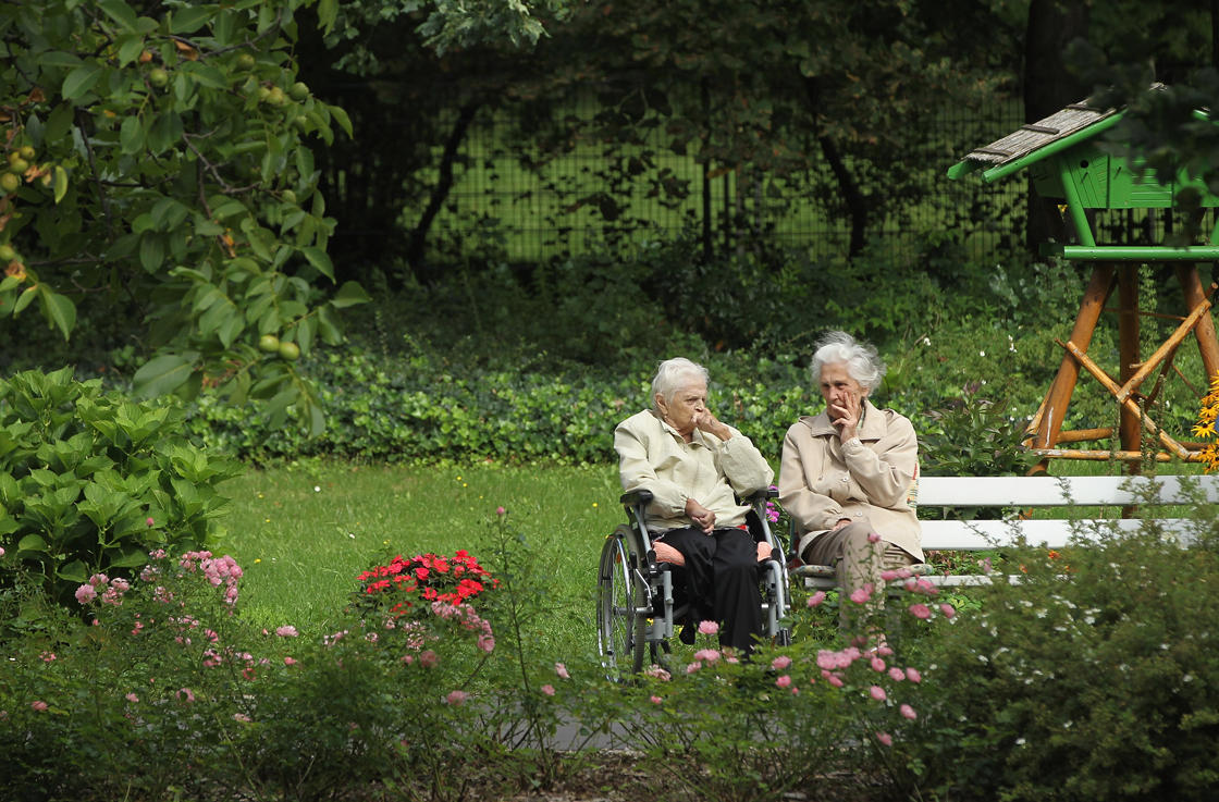 Two elderly women sit and chat in the gardens of the Sewanstrasse senior care home in Lichtenberg district on August 30, 2011 in Berlin, Germany.