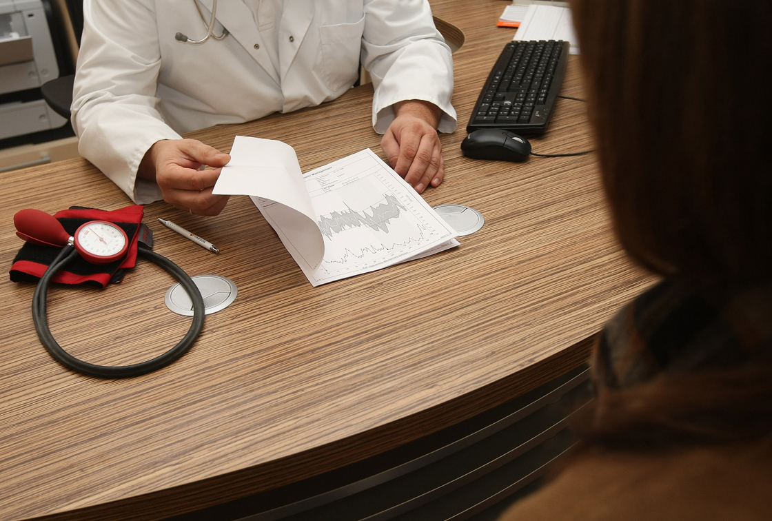 A doctor looks over his notes while talking to a patient.