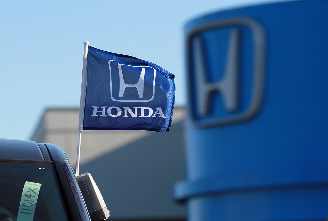 A flag with the Honda logo is displayed on brand new car at a dealership on December 2, 2011.