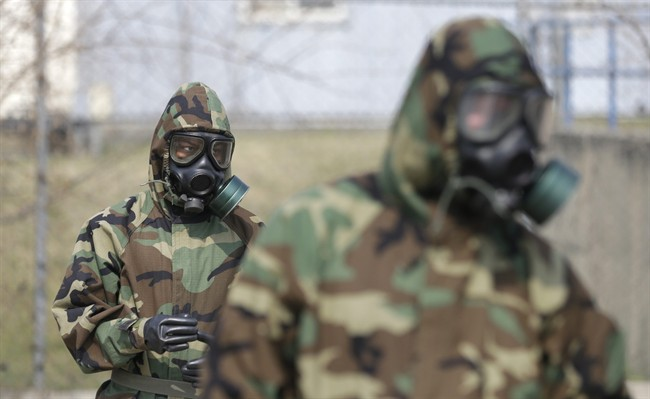 FILE: Soldiers wearing gas masks.