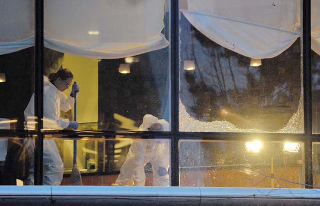 Workers clean up a restaurant at the Wall Centre after long-time gangster Sandip (Dip) Duhre was gunned down execution-style by someone he was meeting.
