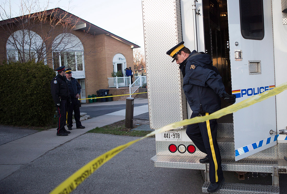 RCMP officers stand outside the Toronto home of one of the two men accused of plotting a terror attack on a rail target, on Monday April 22, 2013.