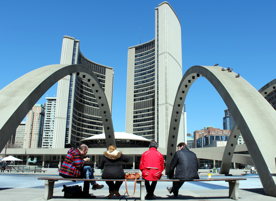 People sit outside of Toronto City Hall.