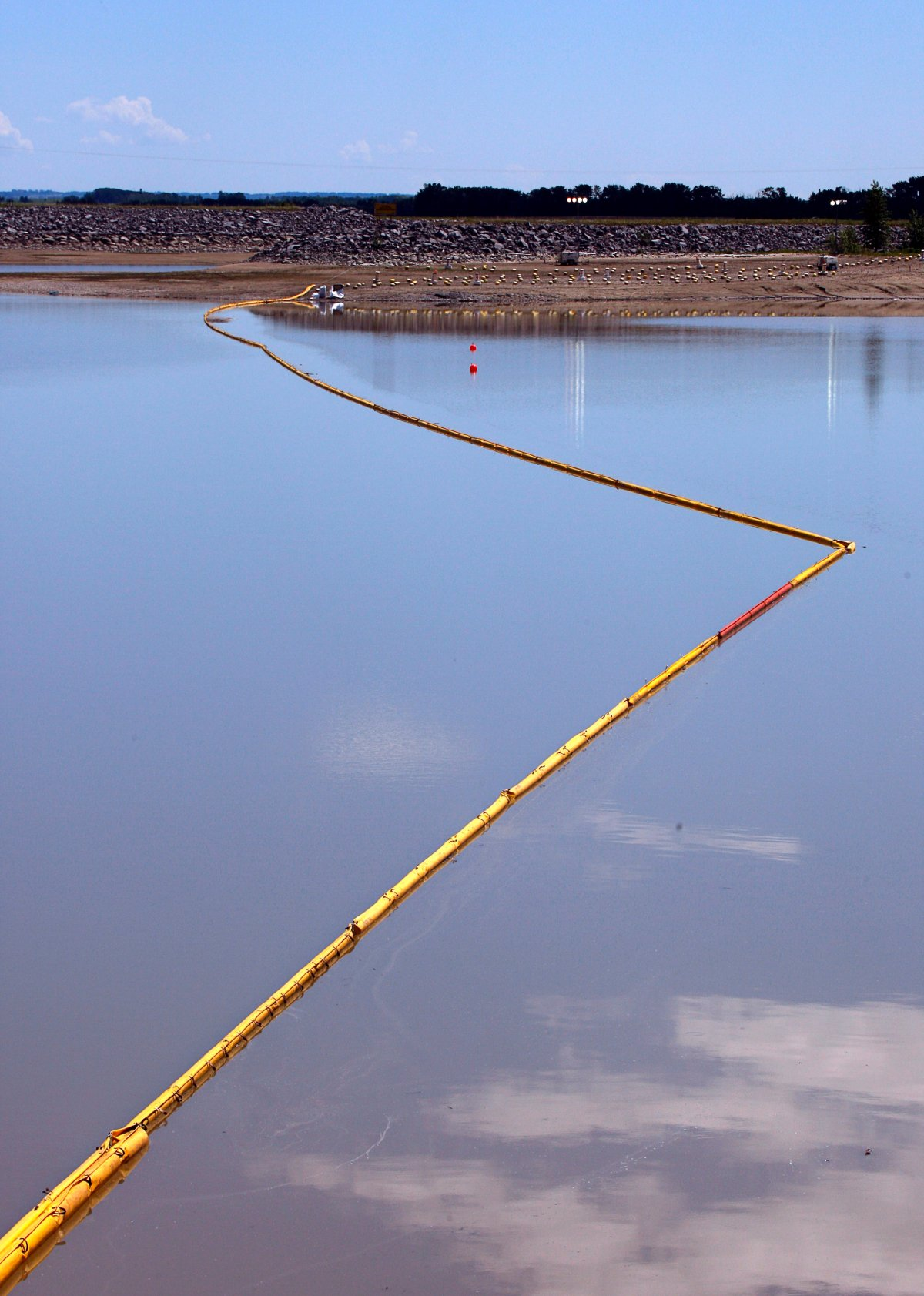 A boom stretches out to contain a pipeline leak on the Gleniffer reservoir near Innisfail, Alta., Tuesday, June 12, 2012.