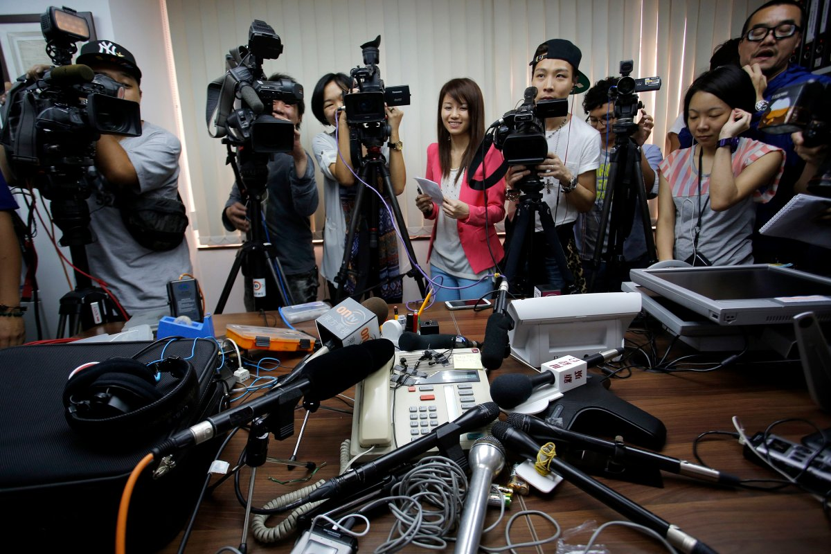 Reporters crowd around a speakerphone as they listen to a transgender woman on it after she won a legal ruling at Hong Kong's top court allowing her to marry, in Hong Kong Monday, May, 13, 2013.