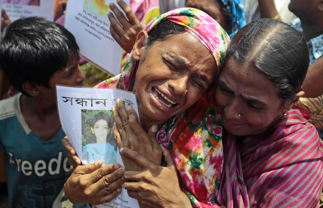 A Bangladeshi woman cries holding the portrait of a missing relative as they gather to offer prayers for the souls of the 1,127 people who died in the garment building structure collapse last month, in Savar, near Bangladesh, Tuesday, May 14, 2013.