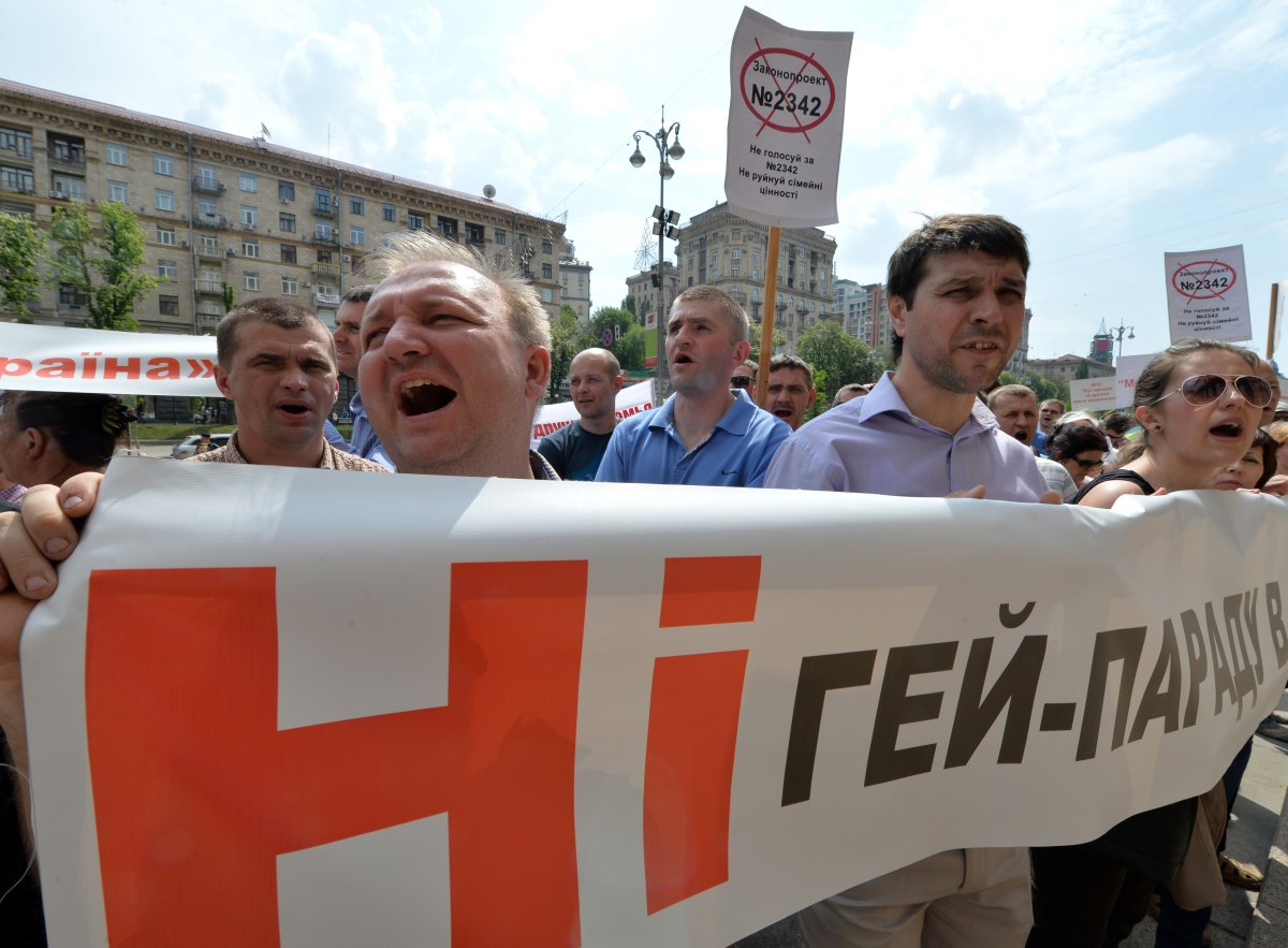 "People shout slogans as they hold placards and a banner reading ""No gay parade!"" during an anti-gay rally in the center of Ukrainian capital of Kiev on May 14, 2013."