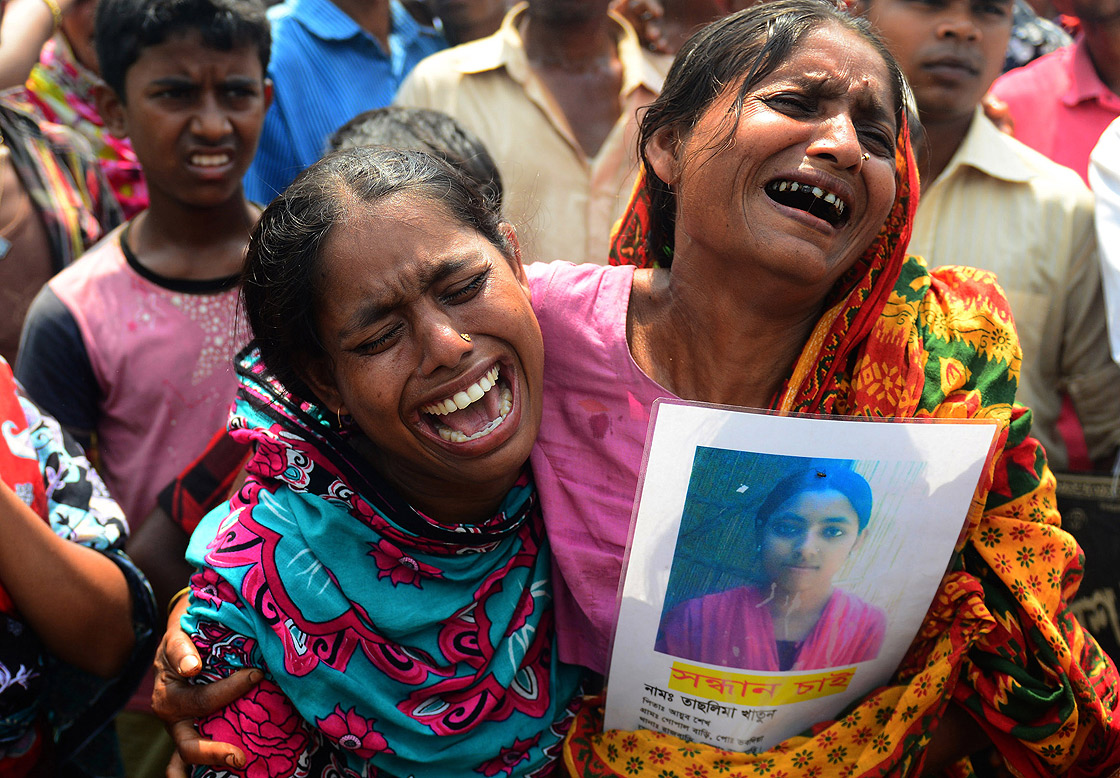 Bangladeshi family members wail for their missing relative, believed to be dead in the rubble of a nine-storey building collapse in Savar, on the outskirts of Dhaka on May 14, 2013.