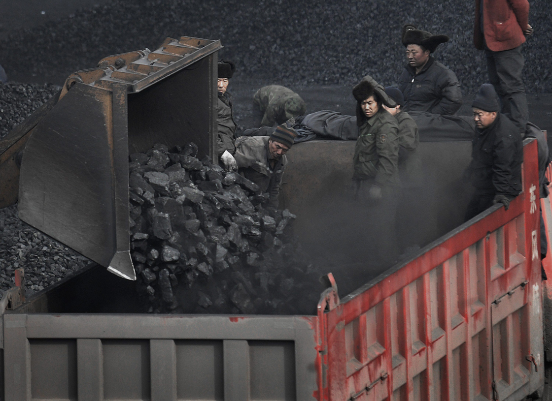 FILE - In this Dec. 3, 2009 file photo, workers load coal into a truck outside a coal mine in Dadong, Shanxi province, China.