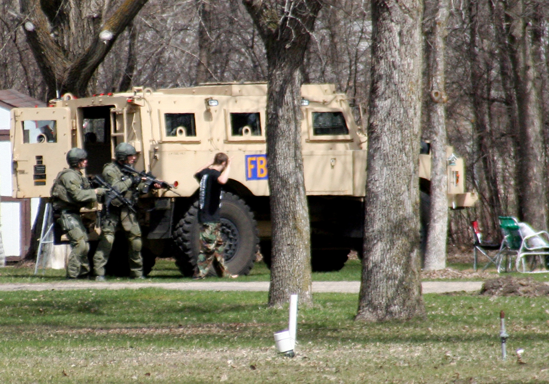 This May 3, 2013, photo provided by Jeremy Jones shows authorities with Buford Rogers, right, during a raid on a mobile home in Montevideo, Minn. Authorities said Monday, May 6, that Rogers was arrested, charged with one count of being a felon in possession of a firearm, and that the agency believes it disrupted a potential terror attack after a search of the home turned up Molotov cocktails, suspected pipe bombs and firearms.