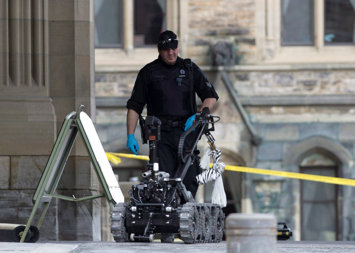 A police officer approaches a police bomb disposal robot holding a suspicious package on Parliament Hill in Ottawa on Thursday, March 28, 2013.