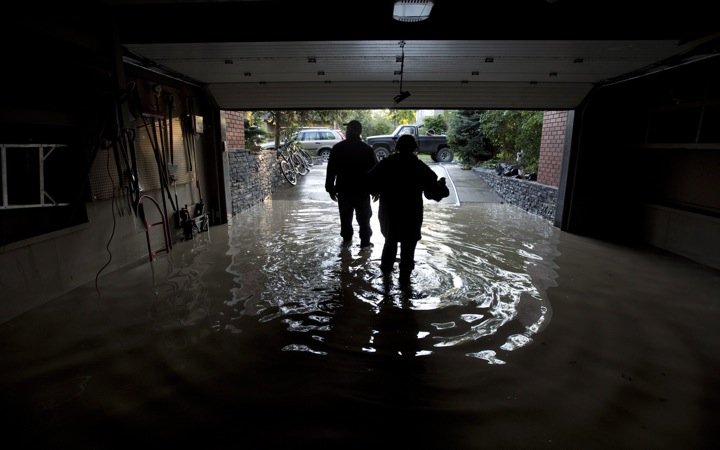 A couple is silhouetted as they walk out of their flooded garage near the Elbow River in Calgary, Ab. Saturday, June 22, 2013.