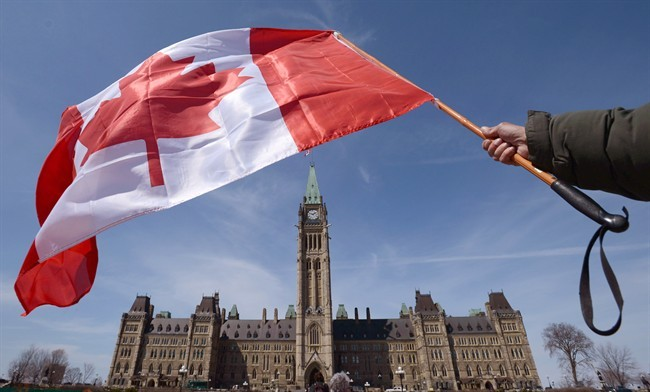A Canadian flag attached to a ski pole is waved on Parliament Hill in Ottawa on Monday, April 15, 2013.