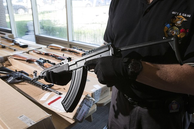 """A police officer from the Toronto Police Integrated Gun and Gang Task Force holds a Czech-made assault rifle as police display guns seized during a series of raids for operation """"Project Traveller"""" at a press conference in Toronto on Friday, June 14, 2013."""