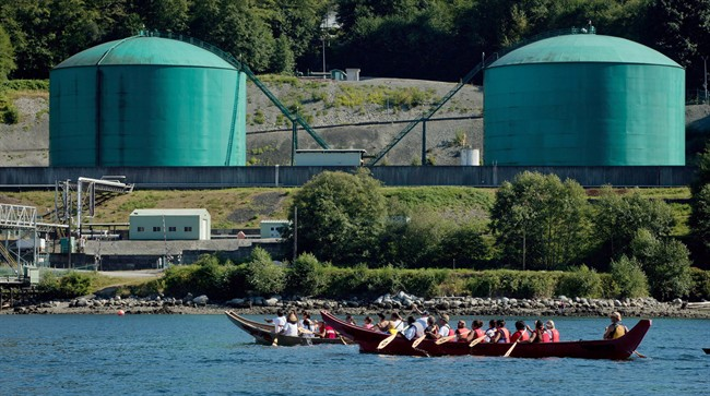 First Nations canoes paddle on the waters of Burrard Inlet to the Kinder Morgan Burnaby Terminal of the Trans Mountain pipeline, in North Vancouver, B.C., on September 1, 2012.