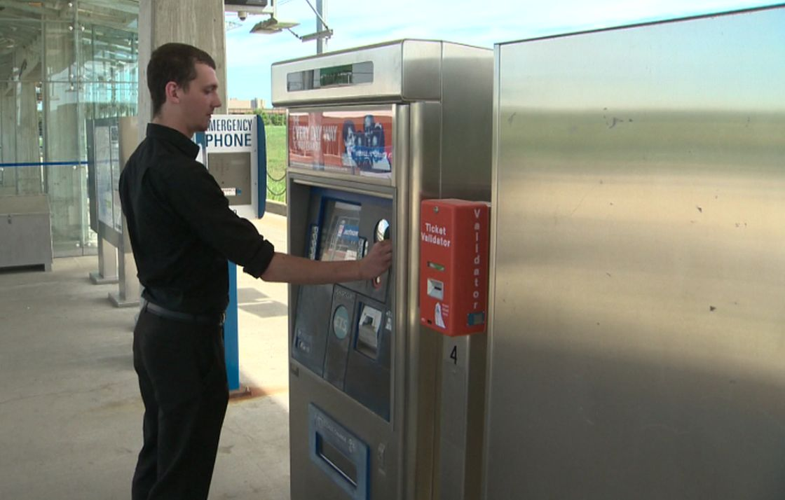 Transit rider Dietrich Neu purchases a ticket at South Campus LRT station.