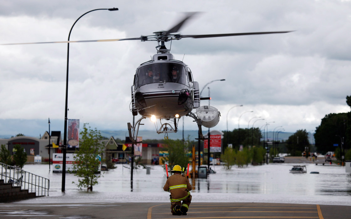 A helicopter carrying evacuated residents lands on a road in High river, Alta. Heavy rains have caused flooding, closed roads, and forced evacuation in High River, Alta., Thursday, June 20, 2013.