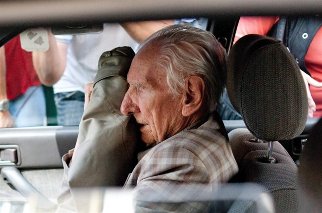 In this Wednesday, July 18, 2012 file photo, alleged Hungarian war criminal Laszlo Csatary sits in a car as he leaves the Budapest Prosecutor's Office after he was questioned by detectives on charges of war crimes during WWII and prosecutors ordered his house arrest in Budapest, Hungary.