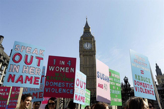 FILE - In this Tuesday, March 5, 2013 file photo people hold banners during a demonstration against domestic violence near Big Ben in London, in the lead up to International Women's Day. About a third of women worldwide have been physically or sexually assaulted by a former or current partner, according to the first major review of violence against women. In a series of papers released on Thursday June 20, 2013 by the World Health Organization and others, experts estimated nearly 40 percent of women killed worldwide were slain by an intimate partner and that being assaulted by a partner was the most common kind of violence experienced by women. (AP Photo/Kirsty Wigglesworth, File).