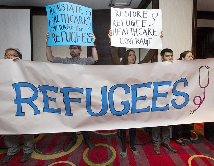 Canadian Doctors for Refugee Care raise a banner.