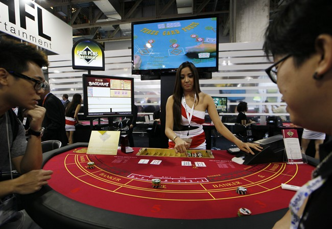 In this file photo taken on Thursday, May 23, 2013, an attendant demonstrates the game of baccarat on a baccarat gaming table during the Global Gaming Expo Asia in Macau.