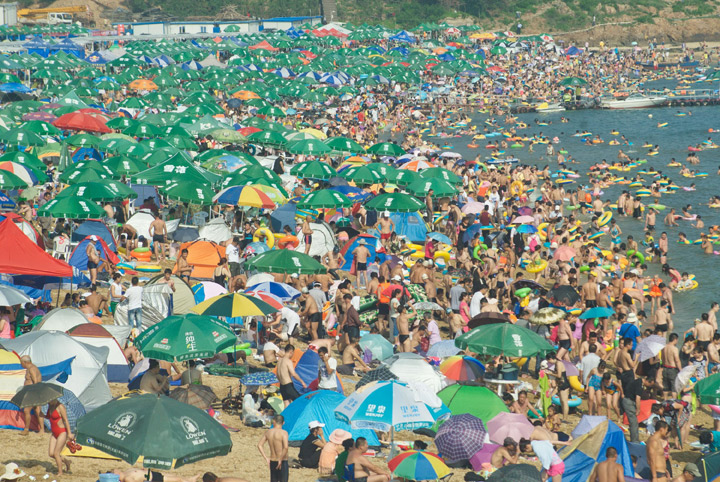 Hundreds of people flock to the beach on July 21 in China as a heat wave gripped much of the country.