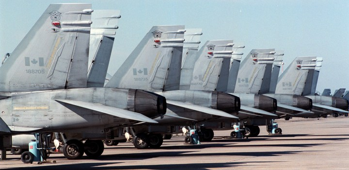 Canadian Air Force CF-18 Hornet jets are parked in a row on a runway at the Canadian Forces Base in Cold Lake, Alberta.