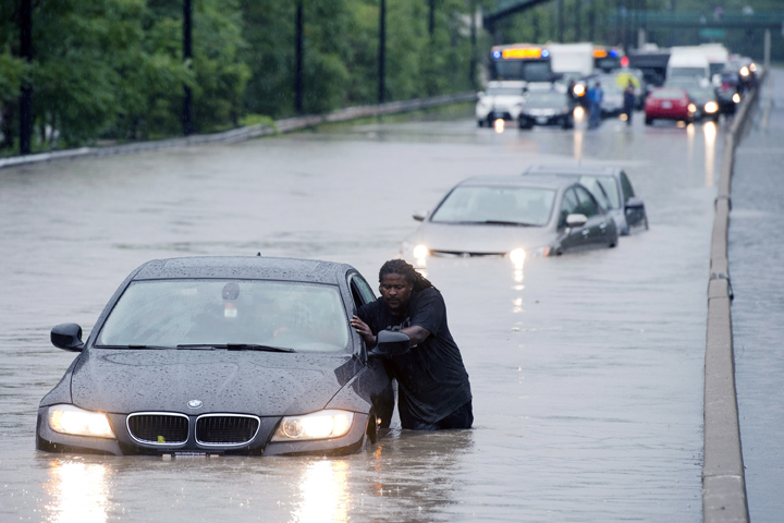A tow truck driver floats a car out of the Don Valley Parkway in Toronto on Monday, July 8 2013. (THE CANADIAN PRESS).