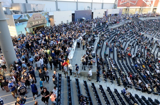Fans walk in the concourse during the second half of the first game at Investors Group Field.