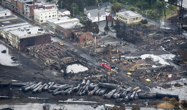 Workers comb through the debris after a train derailed causing explosions of railway cars carrying crude oil Tuesday, July 9, 2013 in Lac-Megantic, Quebec. THE CANADIAN PRESS/Paul Chiasson.