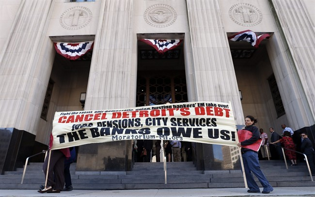 Protesters carry a sign outside the Levin Federal Courthouse in Detroit, Wednesday, July 24, 2013.