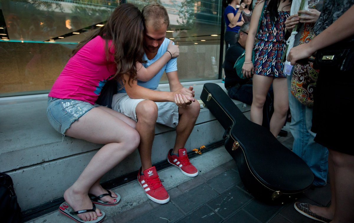 Richard Monteith, second left, cousin of late Canadian actor Cory Monteith, is comforted by a woman during a candlelight vigil outside the Fairmont Pacific Rim Hotel in Vancouver, B.C., on Friday July 19, 2013. Monteith's body was found in a room at the hotel July 13.