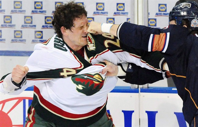 Minnesota Wild left wing Derek Boogaard (24) gets hit by Edmonton Oilers left wing Steve MacIntyre (33) in a fight during first period NHL hockey action in Edmonton on Jan. 30, 2009.