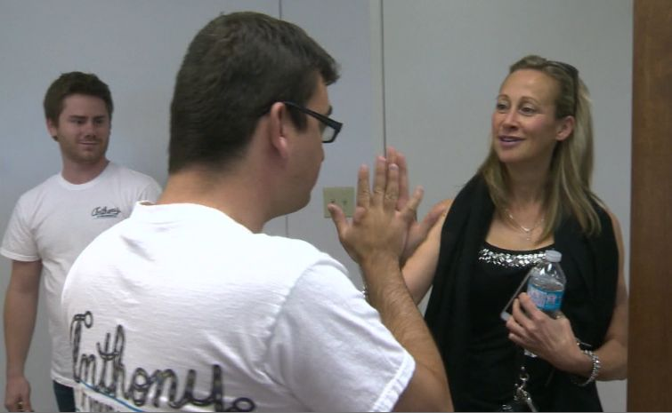 Anthony Barrett gives Julie Brown a high-five as his aide Mikey Hamm looks on.