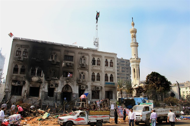 People inspect the burnt Rabaah al-Adawiya mosque with a poster of Egypt's ousted President Mohammed Morsi taped on its antenna in Cairo's Nasr City, Egypt, Thursday, Aug. 15, 2013.