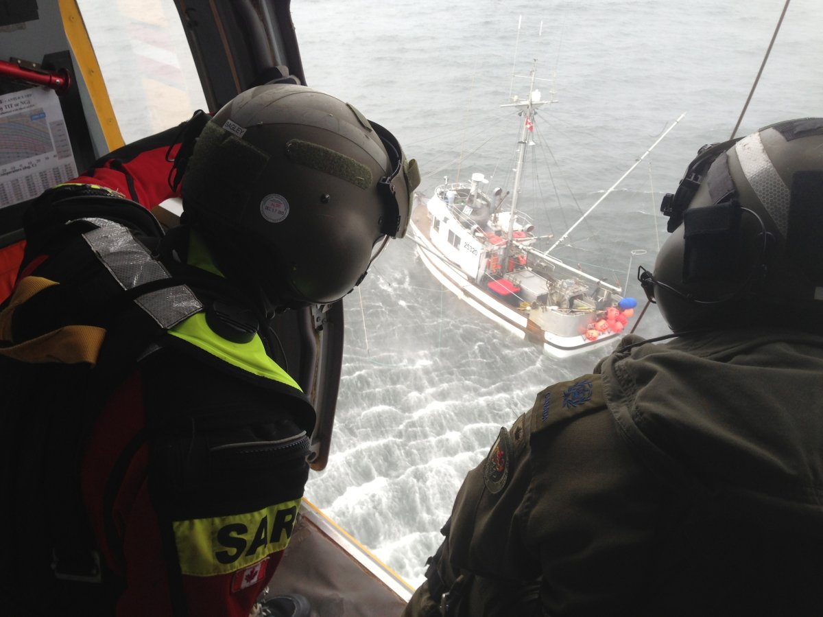An RCAF Search and Rescue Technician (left) and Flight Engineer observe a boat from the rescue door of a CH-149 Cormorant helicopter during a medevac of a fisherman experiencing possible medical distress, Sunday evening, August 11.