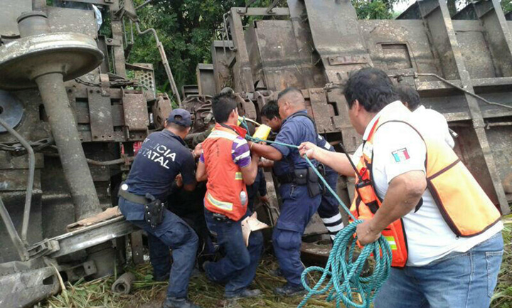 In this photo release by the Civil Protection of the State of Tabasco, police agents and rescue workers work at a site where a train derailed in Tabasco, Mexico, Sunday, Aug. 25, 2013.
