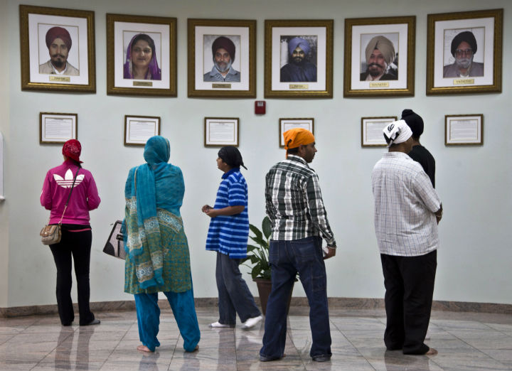 Visitors look at a memorial near the entrance of the Sikh Temple of Wisconsin Wednesday, July 31, 2013, in Oak Creek, Wis. Twelve months ago a white supremacist shot and killed six temple members, and the survivors plan to mark the one-year anniversary with solemn religious rites and a candlelight vigil.
