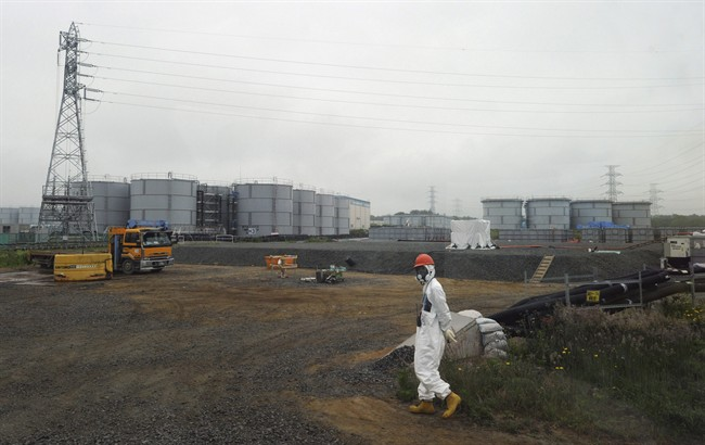 In this Wednesday, June 12, 2013 file photo, a construction worker walks beside the underground water tanks at the Fukushima Dai-ichi nuclear plant at Okuma in Fukushima prefecture, Japan.