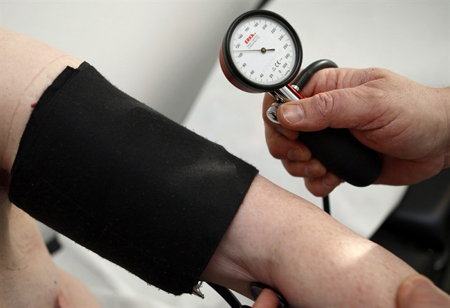 A doctor takes the blood pressure of a man.