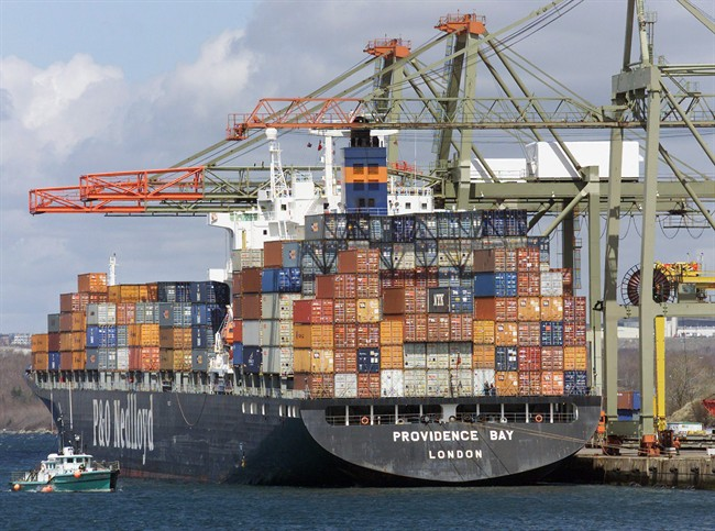A work boat heads past a container ship at the Ceres terminal in Halifax in a file photo.